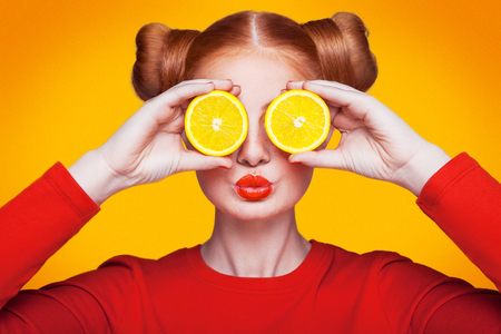 Young beautiful funny fashion model with lemon slice on orange background. with makeup and hairstyle and freckles. holding lemon between eyes with kiss.