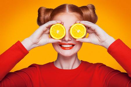 레몬 슬라이스 오렌지 배경으로 젊은 아름 다운 재미 패션 모델. 메이크업 및 헤어 스타일 및 주근깨가있는. 이빨 미소로 눈 사이 레몬을 들고.