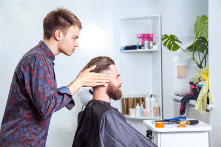 undercut: fashion barber making undercut style for his client. Stock Photo