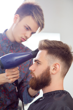 hairstyling: Hairstyling process. Close-up of a barber drying hair of a young bearded man