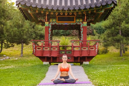 Cheerful young beautiful woman practicing and posing yoga in the east Asian park. baddha konasana pose.
