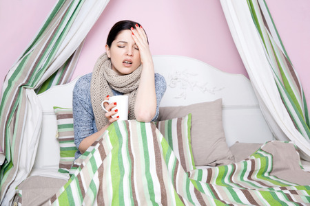 Young beautiful sick woman feeling ill and bad lying on bed suffering headache and temperature trying to rest and sleep on bed.