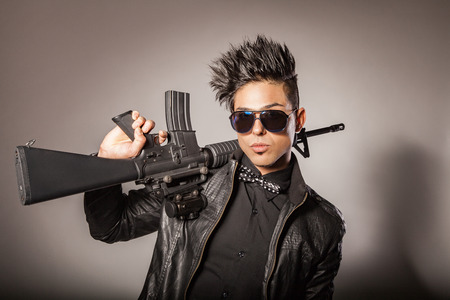 Young middle eastern man with black leather jacket in black suit holding gun. studio shot.