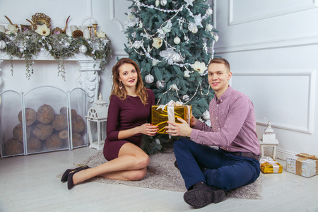 young couple with gifts sitting near new year tree. Stock Photo
