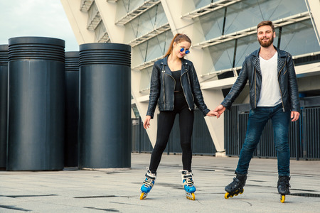 roller blade: Beautiful roller skater couple with hipster style skating after the rain. Stock Photo
