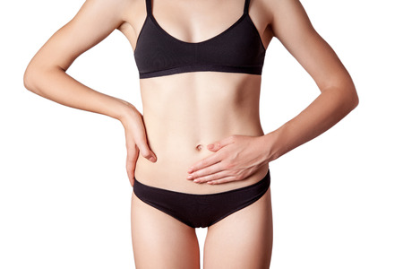 digestion: Closeup view of a young woman with stomach pain or digestion or period cycle . isolated on white background.