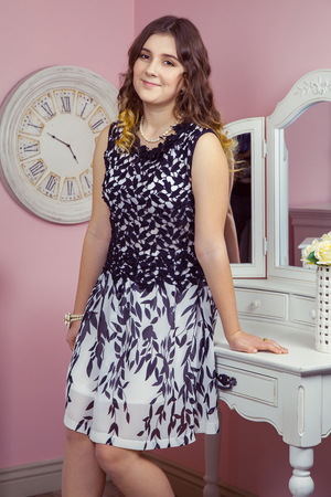 dressing table: Beautiful girl in her room and posing near dressing table, looking at camera.