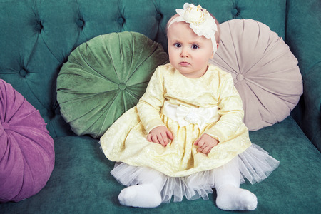 green sofa: Beautiful blonde small girl with yellow dress and flower on her head sitting on green sofa looking at camera.