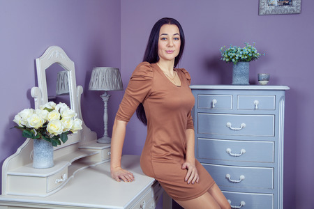 dressing table: Beautiful woman with brown dress and long black hair in her room near her dressing table posing before party. Stock Photo