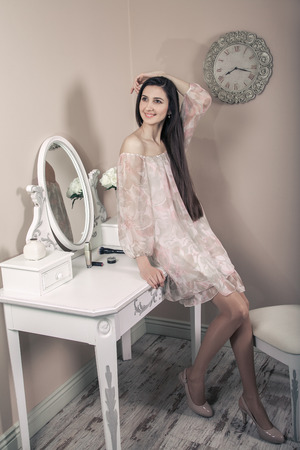 dressing table: Beautiful happy woman with pink dress and long black hair in her room near her dressing table posing before party. Stock Photo