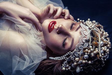 패션 아름다움 젊은 아름 다운 젊은 여자 메이크업 및 그녀의 얼굴에 진주 투 화와 주 근 깨 진주 파란색 배경에 그녀의 얼굴의 앞에 그녀의 머리와 흰