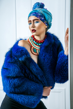 Beauty portrait of fashion model with colored headwear, blue fur coat red eyebrow and lips makeup and necklace. studio shot near windows and white wall. Stock Photo