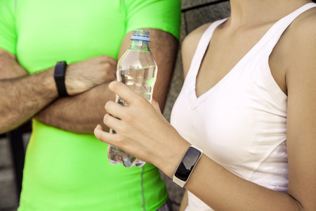 Young sporty couple are resting and check their fitness watch together, drinking water. sport and technology concepts.