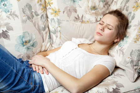 Young beautiful girl with stomach pain lying on the sofa. Stock Photo