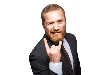 Funny businessman making horn gesture - rock and roll sign. isolated on white background, looking at camera.