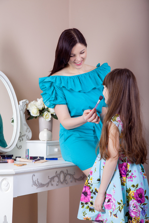 comb: Mother applying makeup to her preteen beautiful daughter at home.