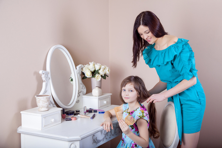 Mother hairdressing her preteen beautiful daughter at home.