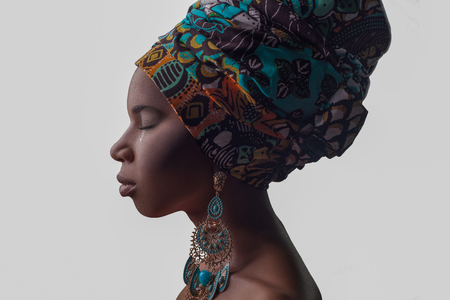 Young beautiful African woman in traditional style with scarf, earrings crying, isolated on gray background. racism, depression or loneliness concept