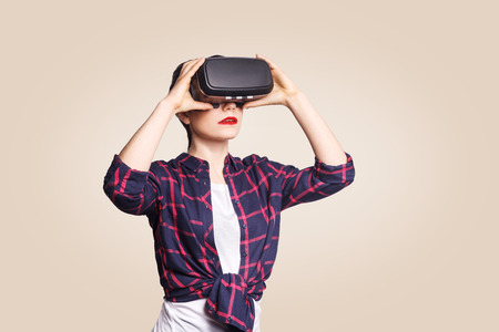 Young beautiful woman in casual style with virtual reality headset on beige background. studio shot.
