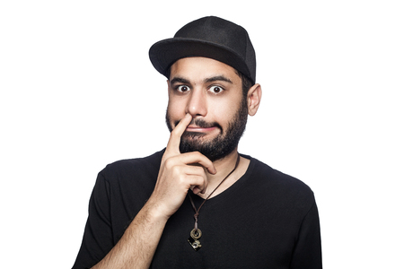Portrait of young uncultured man with black t-shirt and cap looking at camera with finger on his nose. studio shot, isolated on white background.