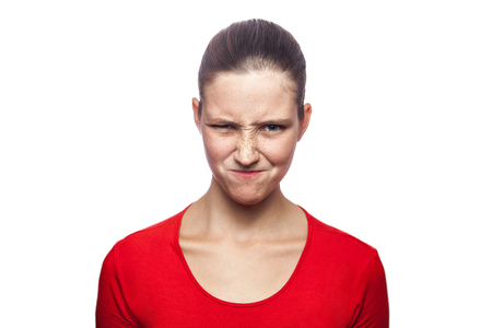 Portrait of cunning woman in red t-shirt with freckles. looking at camera, studio shot. isolated on white background. Stock Photo