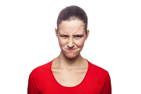 venganza: Retrato de mujer astuta en camiseta roja con pecas. mirando la cámara, tiro del estudio. aislados en el fondo blanco. Foto de archivo