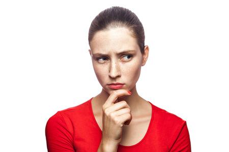 주 근 깨, 촬영 스튜디오와 함께 빨간 티셔츠에 사려 깊은 심각한 여자의 초상화. 흰색 배경에 고립.