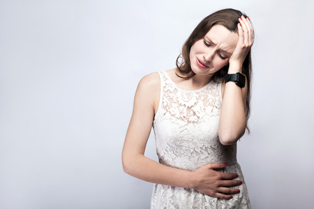 Portrait of beautiful woman with freckles and white dress and smart watch with stomach pain on silver gray background. healthcare and medicine concept. Stock Photo