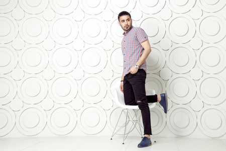 round chairs: Young bearded fashion model in casual style is posing near white circle wall background. studio shot. posing on white chair and looking away.