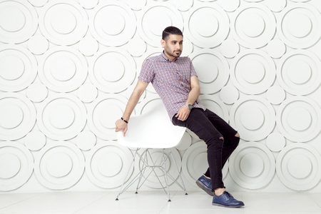Young bearded fashion model in casual style is posing near white circle wall background. studio shot. sitting on chair and looking at away. Фото со стока - 79330139