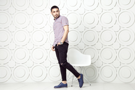 round chairs: Young bearded fashion model in casual style is posing near white circle wall background. studio shot. posing and looking away with hand on packet.