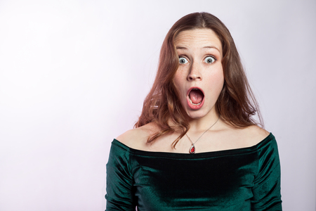 Portrait of shocked woman with freckles and classic green dress. studio shot on silver gray background. Stock Photo