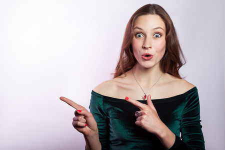 Portrait of surprised shocked woman with freckles and classic green dress showing empty space with finger. studio shot on silver gray background. Stockfoto