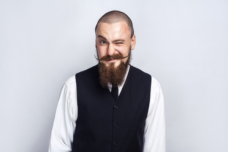 Wink. Handsome businessman with beard and handlebar mustache looking at camera and winking. studio shot, on gray background. Фото со стока - 80328594