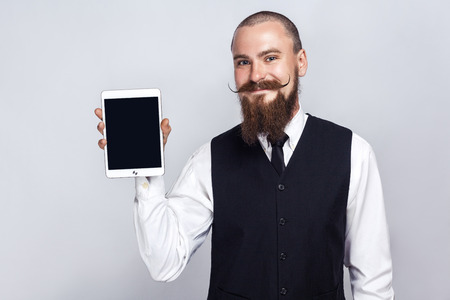 Handsome businessman with beard and handlebar mustache holding digital tablet and looking at camera and showing screen with smiley face. studio shot, on gray background.