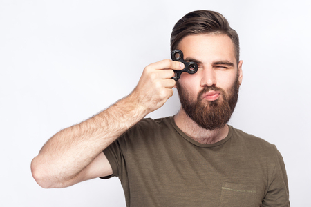 Young man holding and playing with fidget spinner. studio shot on white background. Stock Photo