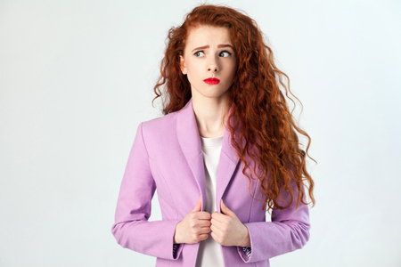 queries: Portrait of thoughtful beautiful business woman with red - brown hair and makeup in pink suit. thinking and looking away, studio shot on gray background. Stock Photo