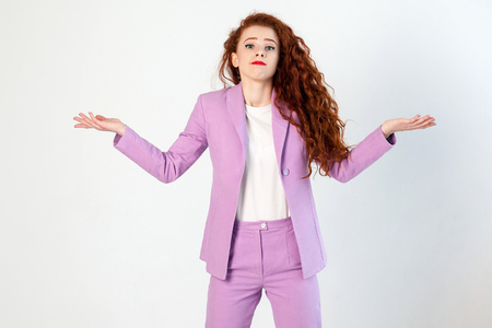 Portrait of  unhappy confused business woman with red - brown hair and makeup in pink suit. looking at camera, studio shot on gray background.