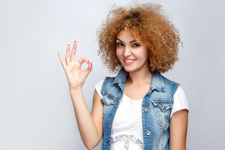 Portrait of beautiful happy curly mixed race girl in casual style with OK sign. studio shot on light gray background.
