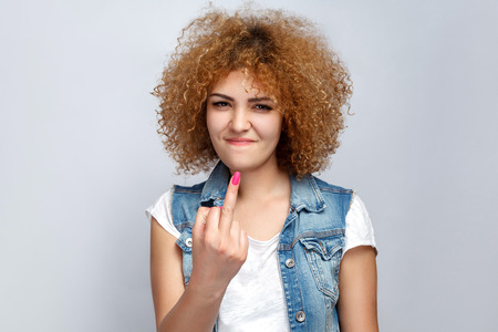 Portrait of crazy curly mixed race girl in casual style is showing middle finger and looking at camera. studio shot on light gray background. Фото со стока