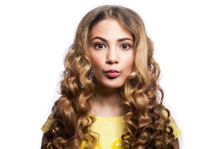 love blow: Portrait of funny kissing girl with wavy hairstyle and yellow t shirt. studio shot isolated on white background. Stock Photo