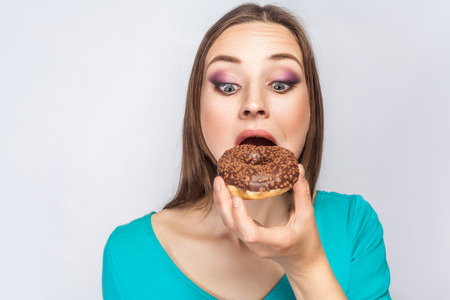 Portrait of beautiful girl with chocolate donuts. looking at donuts and trying to eat. studio shot on light gray background.