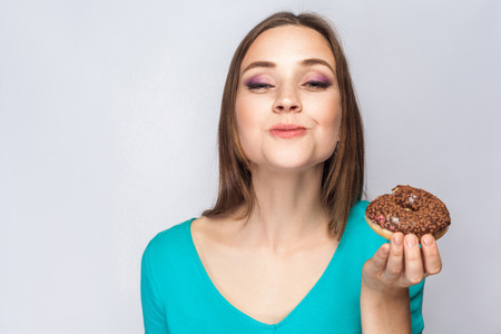 Portrait of beautiful girl with chocolate donuts. eating and looking at camera with funny face. studio shot on light gray background. Stock Photo