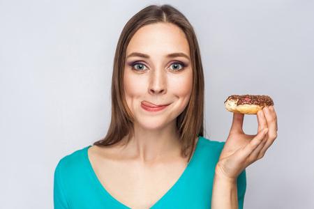 아름 다운 소녀와 초콜릿 도넛의 초상화입니다. enjoing 하 고 혀를 카메라를 찾고. 스튜디오는 밝은 회색 배경에 쐈어.