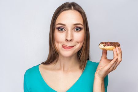 Portrait of beautiful girl with chocolate donuts. enjoing and looking at camera with tongue.  studio shot on light gray background.