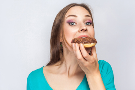 Portrait of beautiful girl with chocolate donuts. eating and looking at camera. studio shot on light gray background.