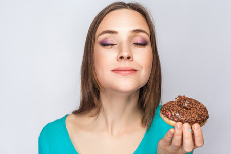 Portrait of beautiful girl with chocolate donuts. eating and enjoing with closed eyes. studio shot on light gray background. Stock Photo