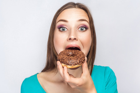 Portrait of beautiful girl with chocolate donuts. trying to eat and looking at camera. studio shot on light gray background.