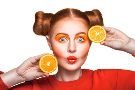 Young beautiful funny fashion model with makeup and hairstyle and freckles. holding orange and looking at camera with kiss. studio shot. isolated on white background. Stock Photo