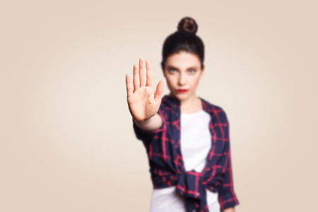 Young annoyed woman with bad attitude making stop gesture with her palm outward, saying no, expressing denial or restriction. Negative human emotions, feelings, body language. Selective focus on hand. Banque d'images